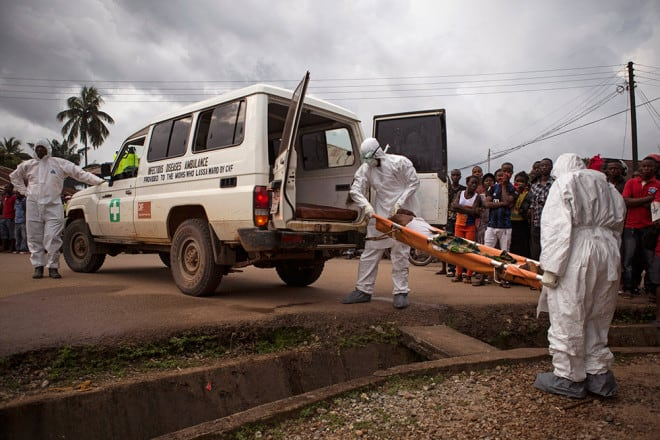 Healthcare workers load a man suspected of suffering from the Ebola virus onto an ambulance in Kenema, Sierra Leone, on Sept. 25, 2014.