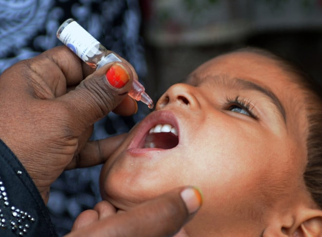 A Pakistani health worker administers polio drops to a child during a polio vaccination campaign in Karachi on January 20, 2015.