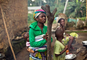 In this photo taken Sunday Nov. 23, 2014, women gather  in the Guinean village of Meliandou, some 400 miles (600 kms) south-east of Conakry, Guinea, believed to be Ebola's ground zero. In Meliandou, as in many other villages across Ebola country, the disease is shrouded in mystery, surrounded by suspicion and rumors. People here still believe that Ebola was disseminated by white people seeking the deaths of blacks, including through a measles vaccination campaign; by a laboratory testing bats to create a vaccination against the virus; by politicians from a rival tribe bent on killing off the forest people; by white miners looking to exploit a nearby mountain of iron ore. (AP Photo/Jerome Delay)